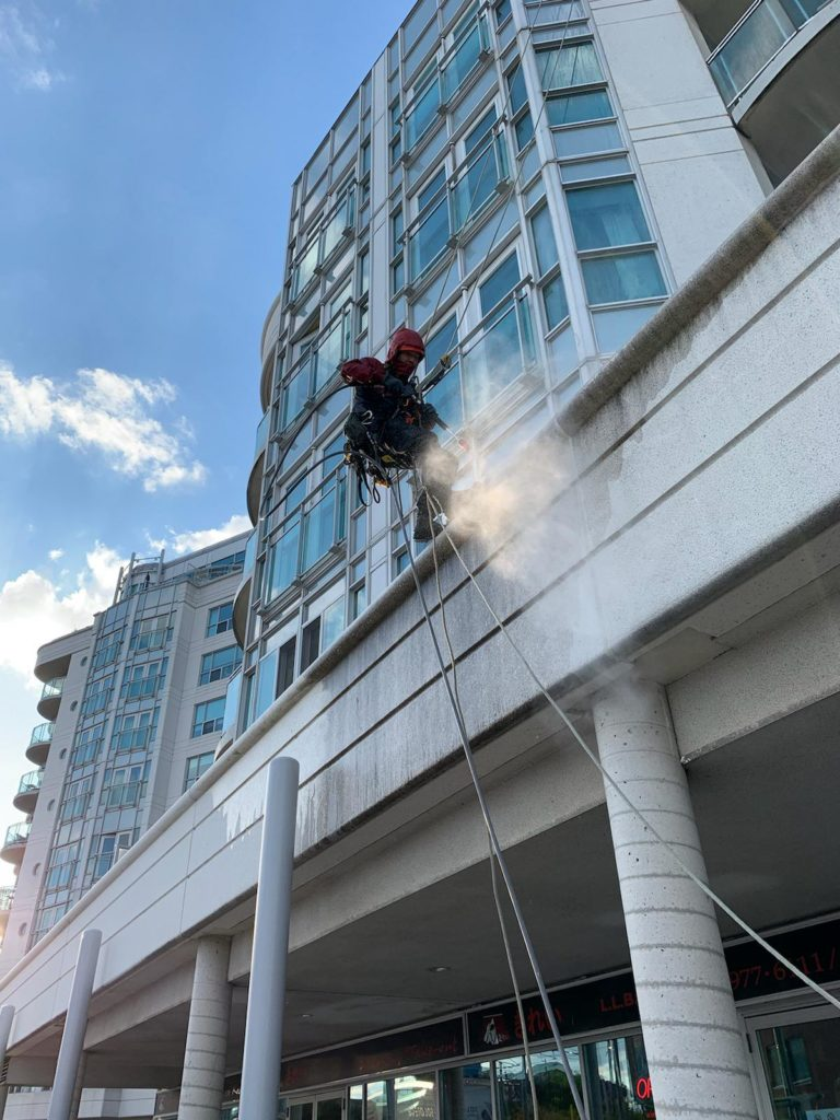 rope access technician cleaning the building